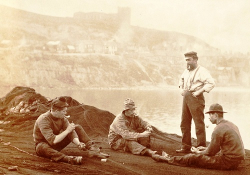 Two fishermen in this scene, 1890, wear the iconic hand-knitted fisherman's blue gansey, a warm, comfortable and durable garment.